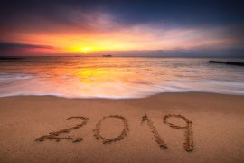 Photo of a beach with the year 2019 written in the sand.