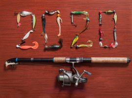 Fishing reel under fishing lures that spell out 2020